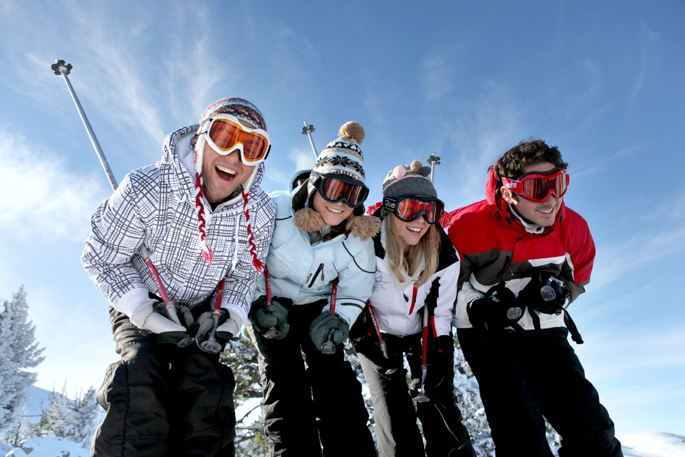 4 teens smiling ski slopes